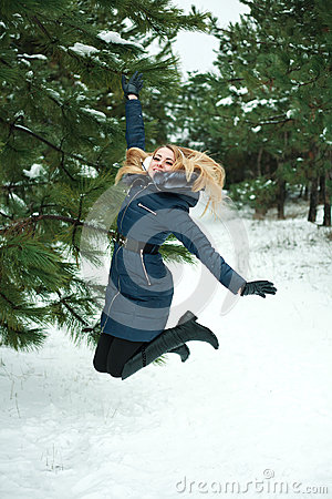 Smiling girl jumping in pinewood
