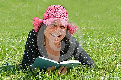Smiling girl lying on a meadow reads a book