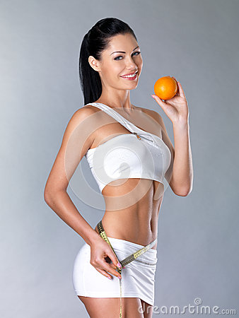 Smiling girl measures figure with an orange