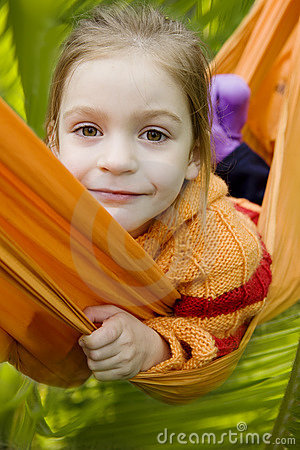 Smiling girl in orange hammock in forest
