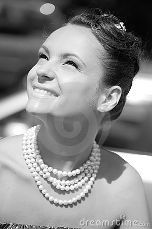 Smiling girl with pearl necklace, monochrome