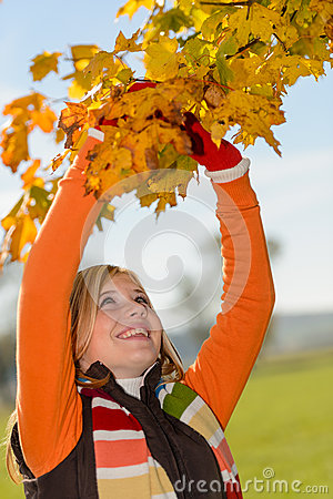 Smiling girl picking dry leaves autumn tree