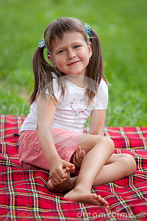 Smiling girl preschooler sitting on plaid in park