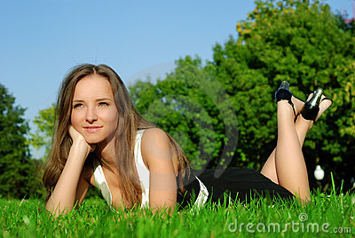 Smiling girl relaxing outdoors on the grass