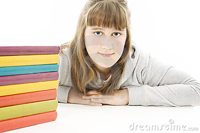 Smiling girl with school books on the table.