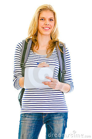 Smiling girl with schoolbag writing in notebook