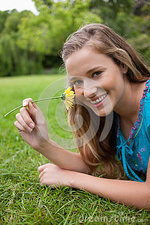 Smiling girl smelling a yellow flower while lying