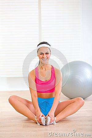Smiling girl in sportswear sitting in yoga pose