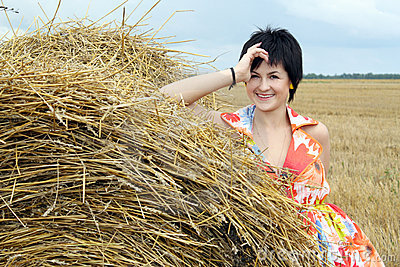 Smiling girl at a stack of straw