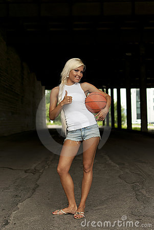 Smiling girl standing with basketball, thumbs up