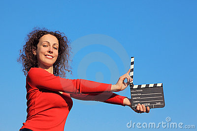 Smiling girl standing with clapperboard
