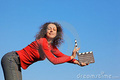 Smiling girl standing in hands clapperboard