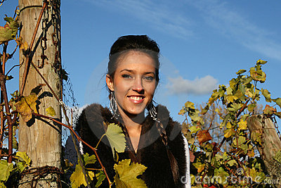 Smiling girl standing in a vineyard