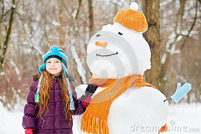 Smiling girl stands next to snowman in orange hat and scarf