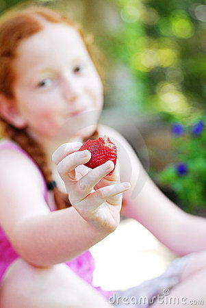 Smiling girl with strawberry