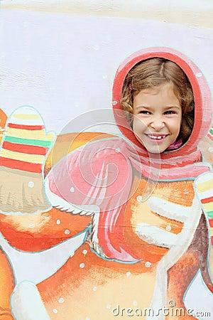 Smiling girl stucks head in plywood scenery at fair