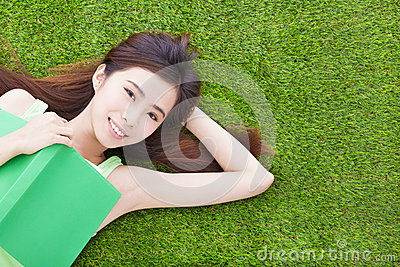 Smiling girl student  laying down  on a meadow