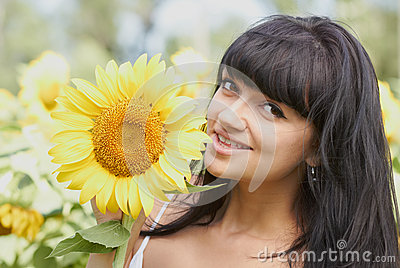 Smiling girl with sunflower outdoors