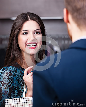 Smiling girl talks to shop assistant