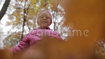 Smiling girl throwing maple leaves in autumn stock video footage