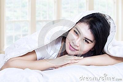 Smiling girl under blanket