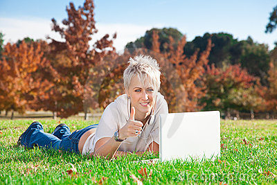 Smiling girl using laptop outdoors