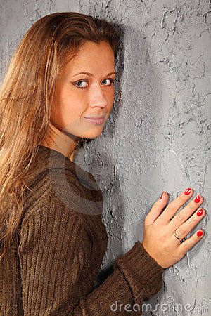 Smiling girl wearing knitted blouse clings to wall