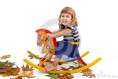 Smiling girl on a wooden horse