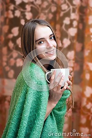 Smiling girl in a woolen blanket drinking coffee