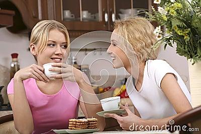 Smiling girls have tea