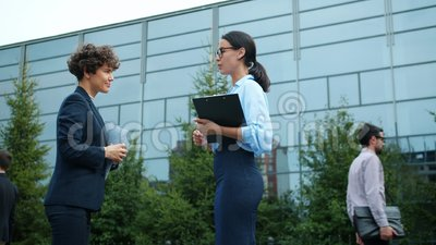 Smiling girls in stylish formal clothing discussing work outdoors near workplace. Smiling girls in stylish formal clothing discussing work standing outdoors near stock footage