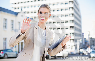 Smiling gorgeous businesswoman holding tablet pc waving