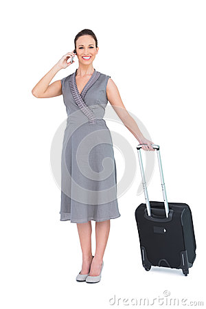 Smiling gorgeous woman carrying her suitcase having phone call