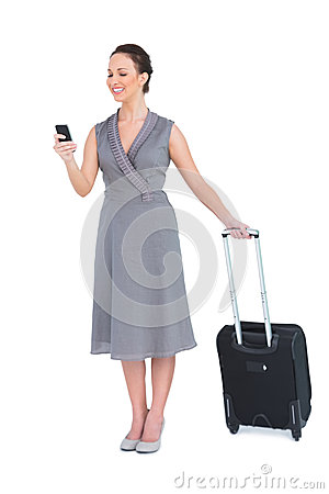 Smiling gorgeous woman with her suitcase texting