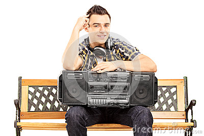 Smiling guy holding a boombox seated on a wooden bench