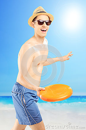 Smiling guy in swimming shorts throwing frizbee, on a beach