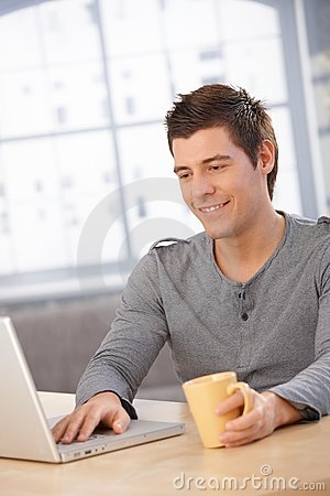 Smiling guy using laptop computer