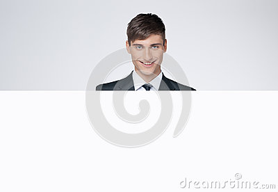 Smiling handsome business man behind white poster.