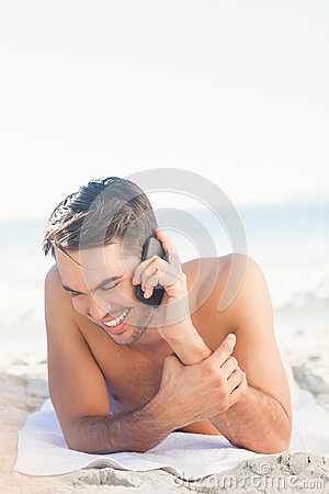 Smiling handsome man on the beach on the phone
