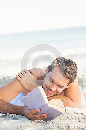 Smiling handsome man on the beach reading