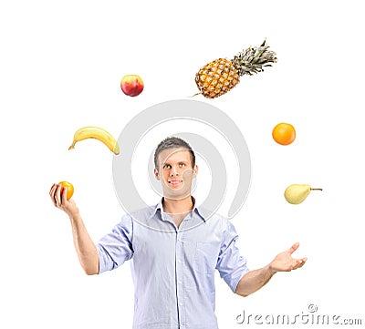 Smiling handsome man juggling fruits