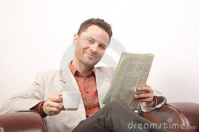 Smiling handsome man, newspaper, cup of coffee