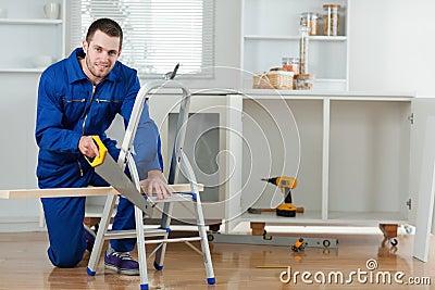 Smiling handyman cutting a wooden board