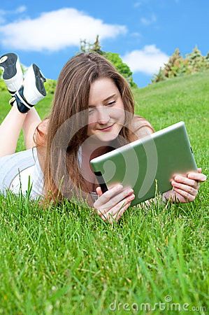 Smiling happy girl lying on grass with tablet.