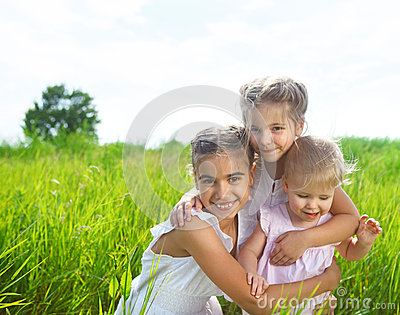 Smiling happy little girls on meadow