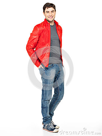 Smiling happy man in red jacket, blue jeans and gymshoes.