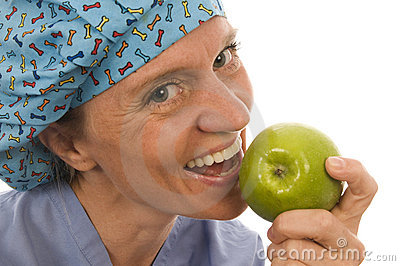 Smiling happy nurse doctor eating green apple