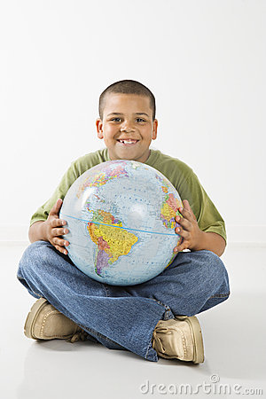 Smiling hispanic boy holding globe.