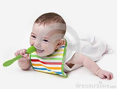 Smiling infant baby with spoon in mouth