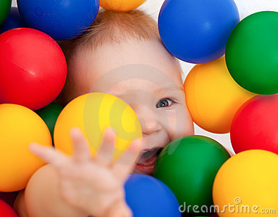 Smiling infant lying among colorful balls